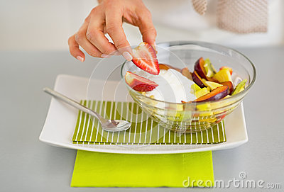 Closeup on woman serving fresh fruit salad