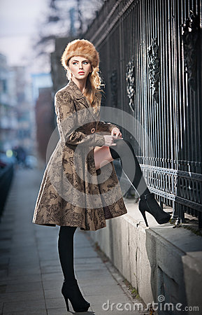 Attractive elegant blonde young woman wearing an outfit with Russian influence in urban fashion shot. Beautiful fashionable girl