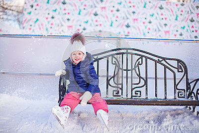 Little girl sitting on a bench in the skating rink