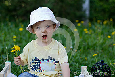 Boy in a park with dandelions in hand