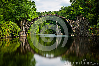 Very old stone bridge over the quiet lake with its reflection in the water