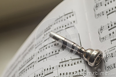 One Silver Trumpet mouthpiece on sheet music book