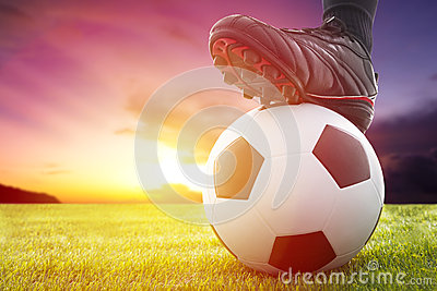 Football or soccer ball at the kickoff of a game with sunset