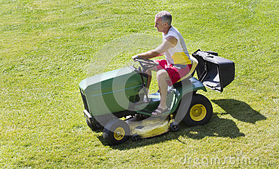 Middle-Aged Man Mowing lawn on riding mower