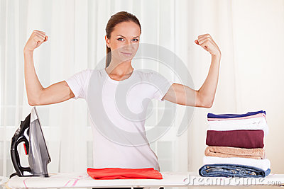 Portrait of smiling housewife ironing clothes.