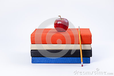 Apple on books and pencil.