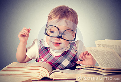Funny baby girl in glasses reading a book