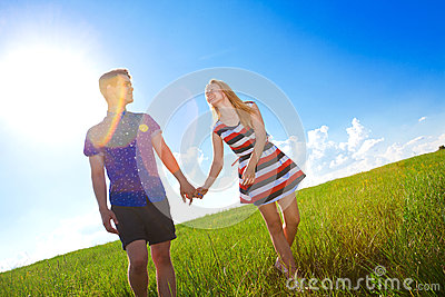 Couple holding hands and walking in green field