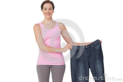 Portrait of a beautiful fit woman holding an old jeans