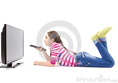 Happy little girl with remote control watching tv