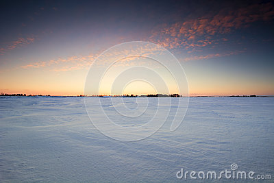 Sunset over a frozen snow covered field.