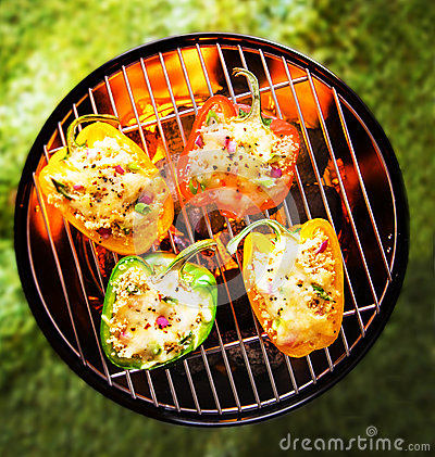Stuffed veggy bell peppers grilling on a BBQ