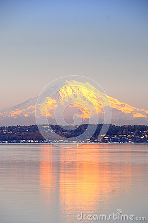 Alpenglow on Mount Rainier reflects on Puget Sound