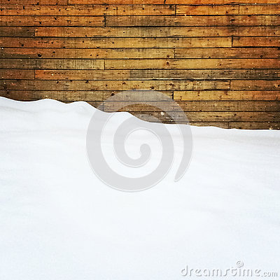 Empty space covered by snow near a wooden wall