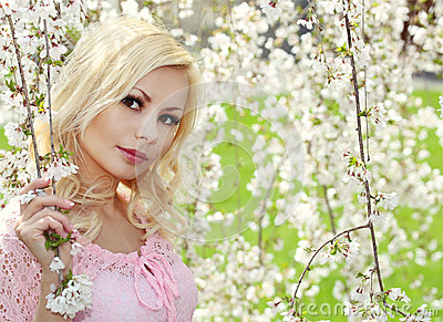 Blonde Girl with Cherry Blossom. Spring Portrait.