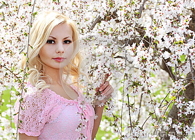 Blonde Girl with Cherry Blossom. Spring Portrait. Beautiful Youn