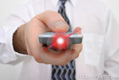 Man's hand on a remote control with light beaming from remote