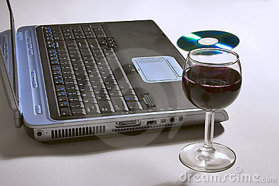 Laptop computer with a glass of wine and CD.