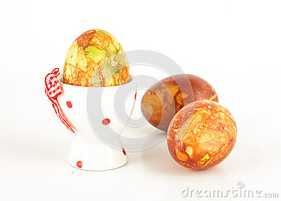Easter egg in the holder and two free rolling painted eggs