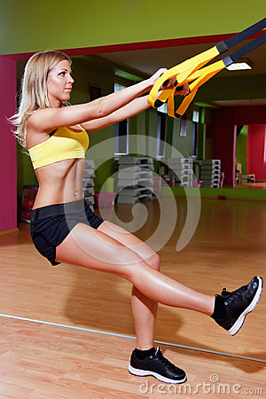 Beautiful young woman doing TRX exercises