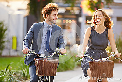 Businesswoman And Businessman Riding Bike Through City Park