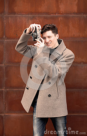 The young man in a coat photographs model the vintage camera at a metal rusty wall