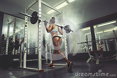 Fitness sexy girl in the gym doing squat on smoke background
