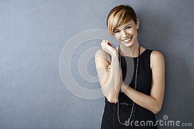 Happy young woman in black dress and pearls