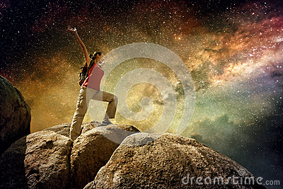 Hiker standing on top of a mountain and enjoying night sky view