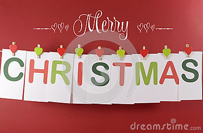 Merry Christmas greeting message across red and green letter cards hanging from heart shape pegs on a line bunting