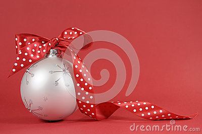 Close up of beautiful white Christmas tree ornament with red polka dot ribbon on red background