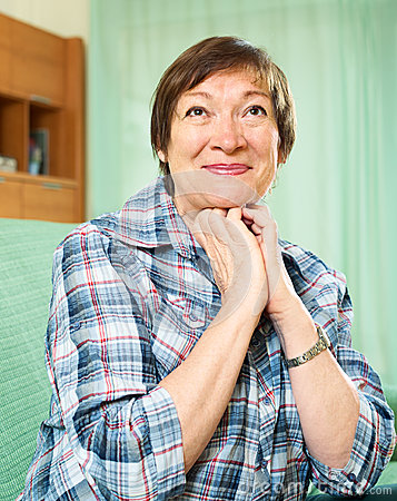 Elderly woman in casual clothes sitting on couch