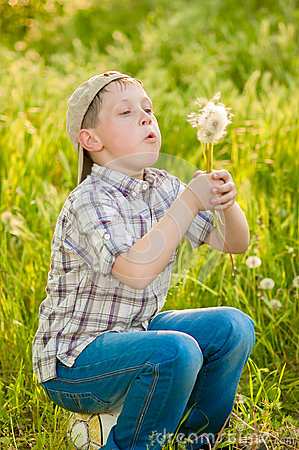 Boy with dandelions in summer