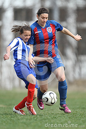 Girls fighting for ball during soccer game