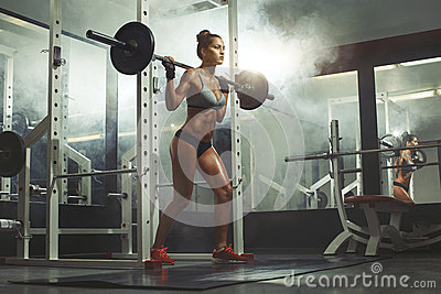 Woman lifting barbell with weight in gym