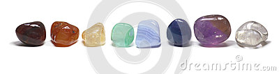 Row of chakra crystals on white