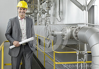 Portrait of confident young male architect holding blueprint by machinery in industry