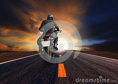 Rear veiw of young man riding big motorcycle on asphalt road against beautiful dusky  sky
