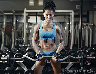 Young brunette girl in the gym doing biceps exercise with barbell