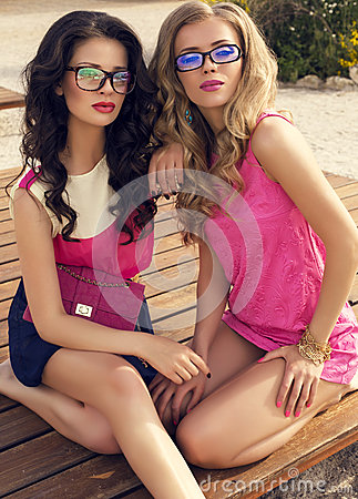 Beautiful girls in glasses posing on beach