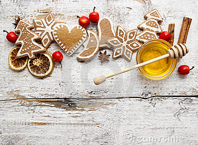 Gingerbread christmas cookies and bowl of honey on wooden table.