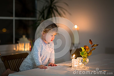 Portrait of little girl watching candles in dark room