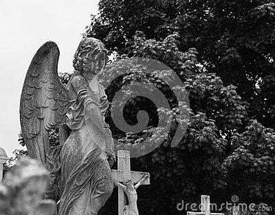 Concrete angel on top of tombstone at cemetery