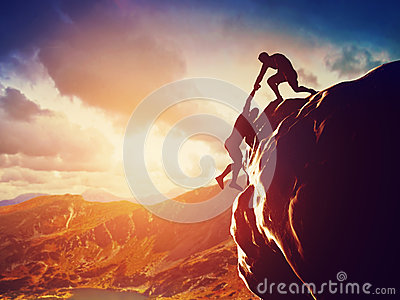 Hikers climbing on rock, giving hand and helping to climb
