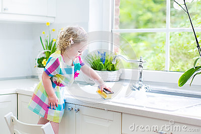 Pretty curly toddler girl in colorful dress washing dishes