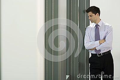Businessman leaning against wall in office, looking through window, thinking, side view