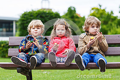 Three siblings sitting on bench and eating chocolate.