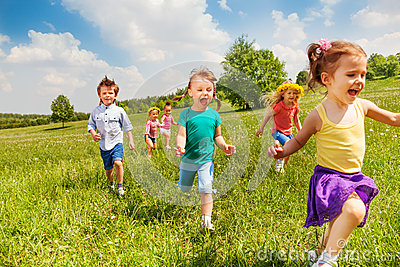 Excited running kids in green field play together