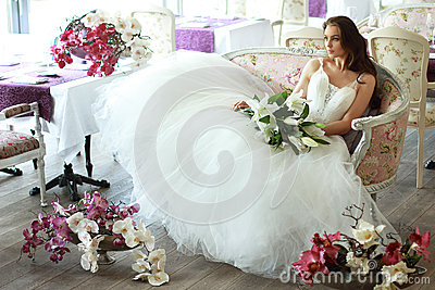 Beautiful bride in a magnificent white wedding dress of tulle with a corset sitting on the sofa with bouquet lily and orchid