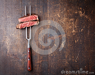 Slices of beef steak on meat fork